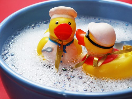 rubber duckies floating in a bucket of soapy water